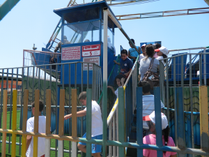 Some excited young patrons board the giant swinging ride.